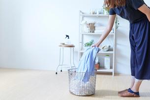 ランドリーラックの前で洗濯籠にシャツを入れる女性の写真素材 [FYI01462864]