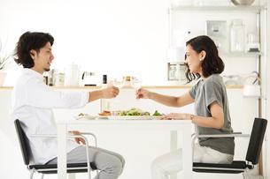 白いダイニングテーブルで食事する男女の写真素材 [FYI01462875]