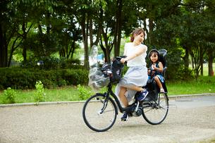 女の子を乗せて自転車で公園内を走るお母さんの写真素材 [FYI01462896]