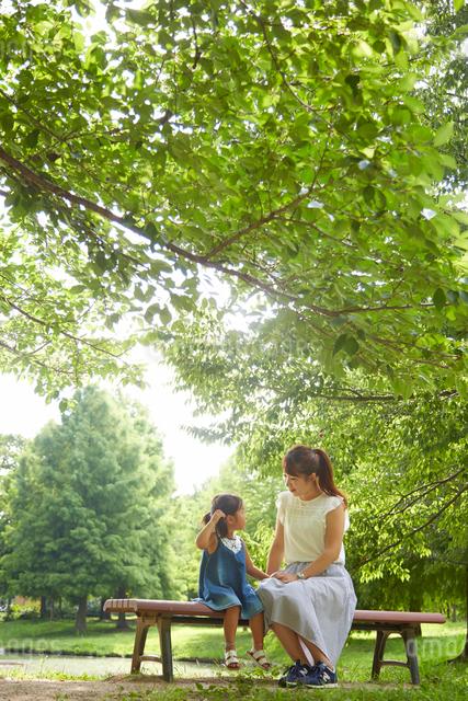 公園内の池の前にあるベンチに座って話をするお母さんと女の子の写真素材 [FYI01462898]