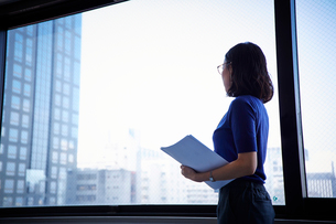 書類を持って窓の外を見つめる女性の写真素材 [FYI01462905]