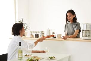 白いダイニングテーブルで食事する男女の写真素材 [FYI01462919]