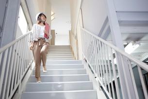 ヘルメットを被り書類を持ちながら階段を下りる女性の写真素材 [FYI01463124]