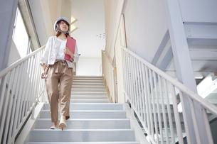 ヘルメットを被り書類を持ちながら階段を下りる女性の写真素材 [FYI01463128]