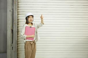 ヘルメットを被り書類を持ちながら指をさす女性の写真素材 [FYI01463135]