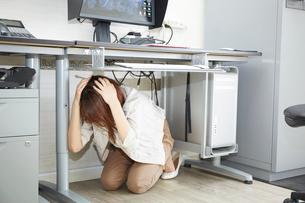 オフィスの机の下に隠れる女性の写真素材 [FYI01463223]