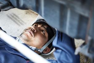 車の下に潜り込み作業をする作業服とヘルメットの男性の写真素材 [FYI01463237]