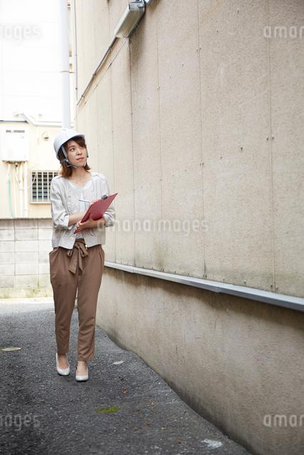 ヘルメットを被り書類を持ちながら点検をする女性の写真素材 [FYI01463242]