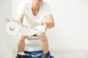 トイレットペーパーを引き出す男性の写真素材 [FYI01463285]