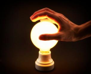 光る電球と男性の手の写真素材 [FYI01463288]