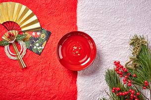 紅白の和紙に置かれた屠蘇の盃と正月飾りの写真素材 [FYI01463290]