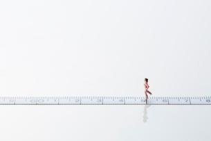 メジャーの上を走るミニチュア人形の女性の写真素材 [FYI01463292]
