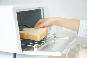 トースターでパンを焼く女性の写真素材 [FYI01463304]