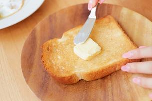 テーブル上でパンにバターを塗っている様子の写真素材 [FYI01463330]