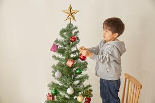 椅子を台にしてクリスマスツリーの飾り付けをする男の子の写真素材 [FYI01463340]