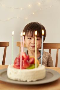 お祝いのケーキのろうそくを見つめる男の子の写真素材 [FYI01463343]