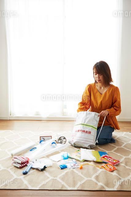 防災グッズを準備している女性の写真素材 [FYI01463370]