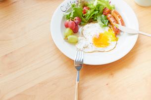 ダイニングテーブルの上の食べかけの朝食プレートの写真素材 [FYI01463371]