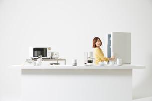 AIスピーカーが置いてあるキッチンで冷蔵庫を開ける女性の写真素材 [FYI01463374]