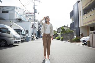 ヘルメットを被り書類を持ちながら道に立つ女性の写真素材 [FYI01463395]