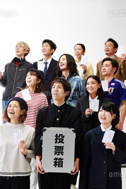 上を見ている投票箱を持つ男子学生と投票用紙を持つ人々の写真素材 [FYI01463464]