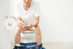 トイレットペーパーと携帯を操作する男性の写真素材 [FYI01463468]