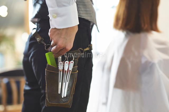 腰袋の中の道具に手を添える美容師の写真素材 [FYI01463470]