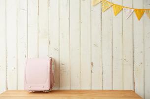 ガーランドが飾ってある板壁の前に置かれたピンクのランドセルの写真素材 [FYI01463481]