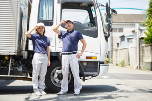 大きなトラックの前で決めポーズをする働く男女の写真素材 [FYI01463504]