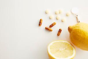 白い天板の上に置かれたレモンとビタミン剤とミニチュア人形の写真素材 [FYI01463555]