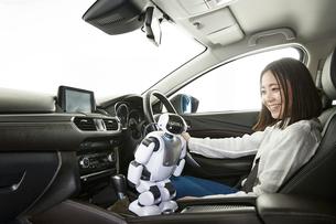 ロボットを使って自動運転車を操作する女性の写真素材 [FYI01463575]