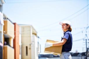 住宅街で段ボールを抱えてたたずむ作業着の女性の写真素材 [FYI01463611]