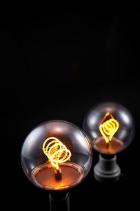 黒い背景の上にあるふたつの電球の写真素材 [FYI01463645]