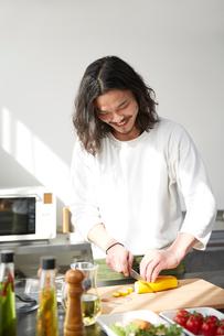 キッチンで野菜を切る笑顔の男性の写真素材 [FYI01463670]