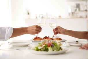 白いダイニングテーブルで食事する男女の写真素材 [FYI01463707]