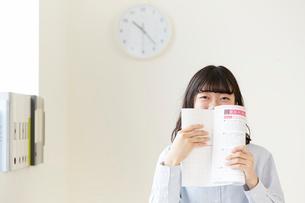 参考書で口元を隠しながら笑う女子高生の写真素材 [FYI01463719]