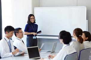 プレゼンをしている女性と話し合う社員の写真素材 [FYI01463745]