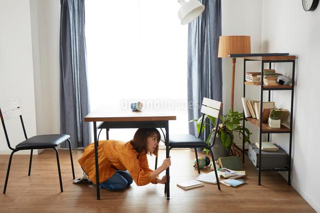 自宅にいるときに地震がきて怯える女性の写真素材 [FYI01463771]