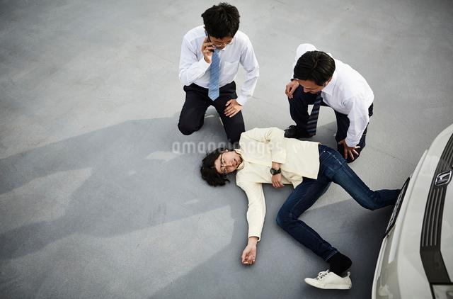 車の前に倒れている男性と様子を伺う二人の男性の写真素材 [FYI01463775]