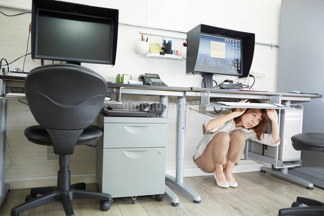オフィスの机の下に隠れる女性の写真素材 [FYI01463793]