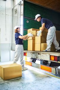 トラックから段ボール箱を積み降ろす作業服の男女の写真素材 [FYI01463808]