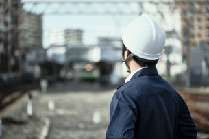 線路に立つ作業服とヘルメットの男性の写真素材 [FYI01463812]