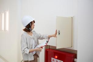 ヘルメットを被り書類を持ちながら点検をする女性の写真素材 [FYI01463816]