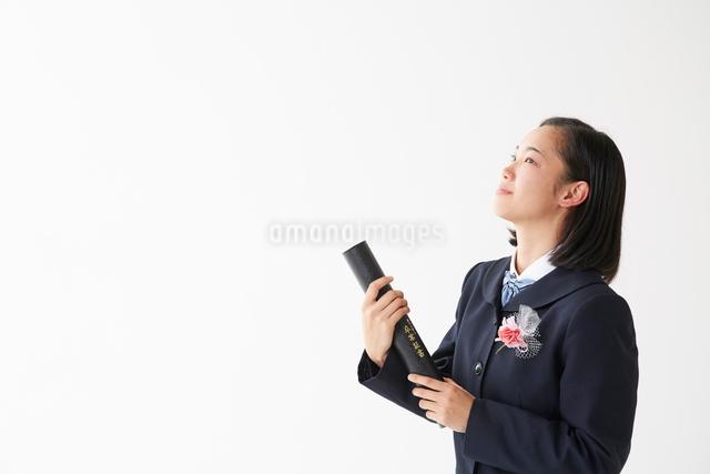 卒業証書の筒を持って上を見上げる女子高生の写真素材 [FYI01463821]