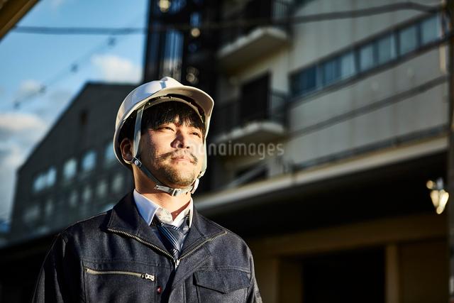 遠くを見ている作業服とヘルメットの男性の写真素材 [FYI01463823]
