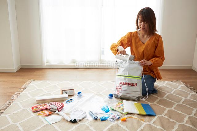 防災グッズを準備している女性の写真素材 [FYI01463833]