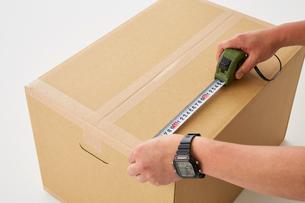 ダンボールの大きさをスケールで測る男性の手の写真素材 [FYI01463838]