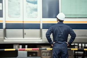 遮断機の前に立つ作業服とヘルメットの男性の写真素材 [FYI01463851]