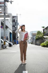 ヘルメットを被り書類を持ちながら道に立つ女性の写真素材 [FYI01463858]