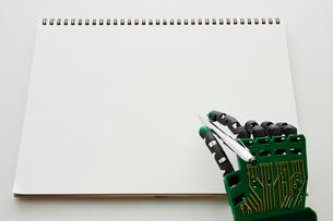 スケッチブックとペンを持ったロボットの手の写真素材 [FYI01463868]